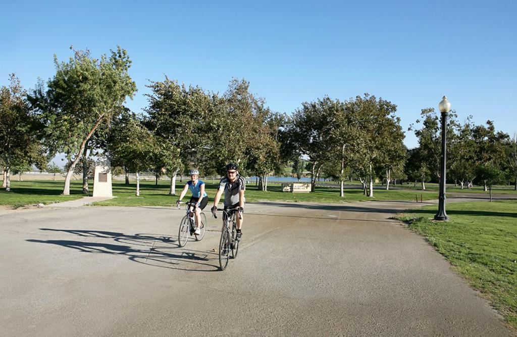 Man and woman with helmets on riding bike near Glen Helen lake.