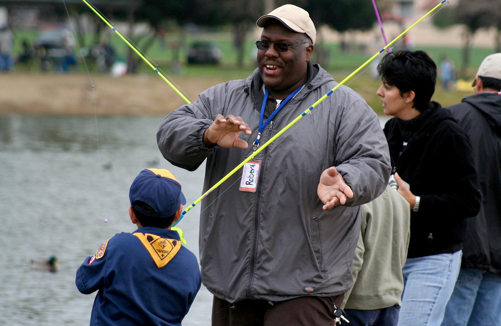 Man helping children fish at Guasti park.