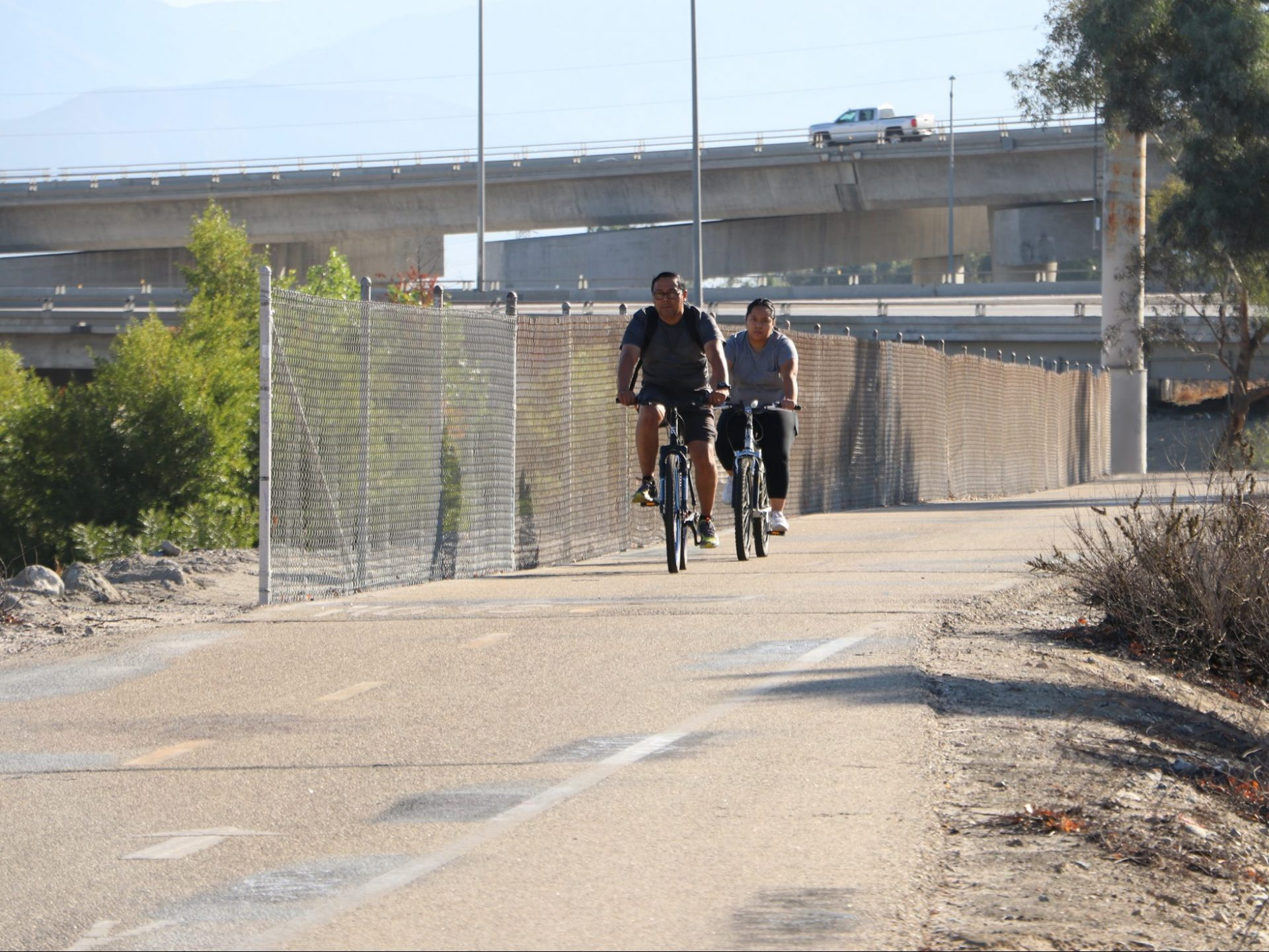 2 Adults riding on a paved trail