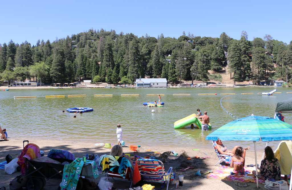 A summer photo of adults and children laying on the sand watching swimmers in the lake.