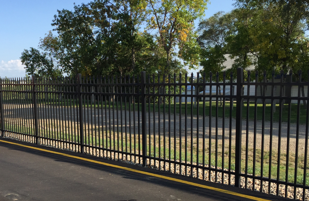 Black iron fence with grass and empty lot in background.
