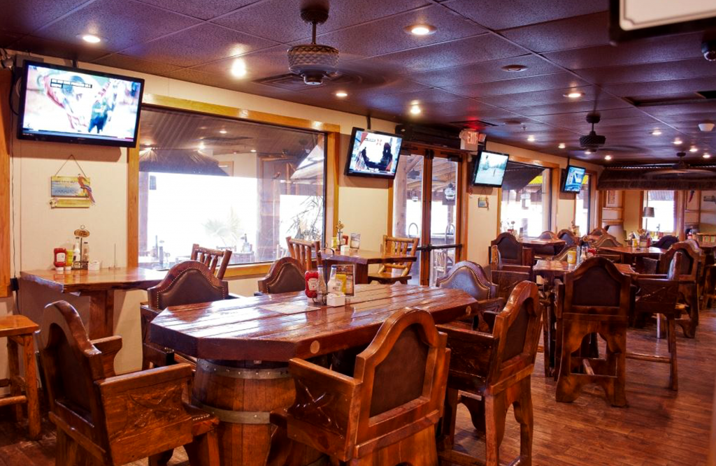Inside the Pirates Cove restaurant. Wooden tables and chairs with TV screens on the wall.
