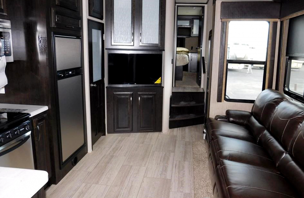 Upscale RV shows leather couch and stainless steel appliances.