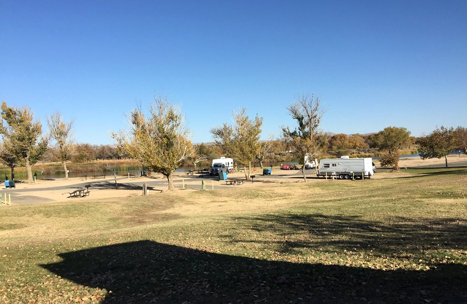 A large grass area with RVs parked.