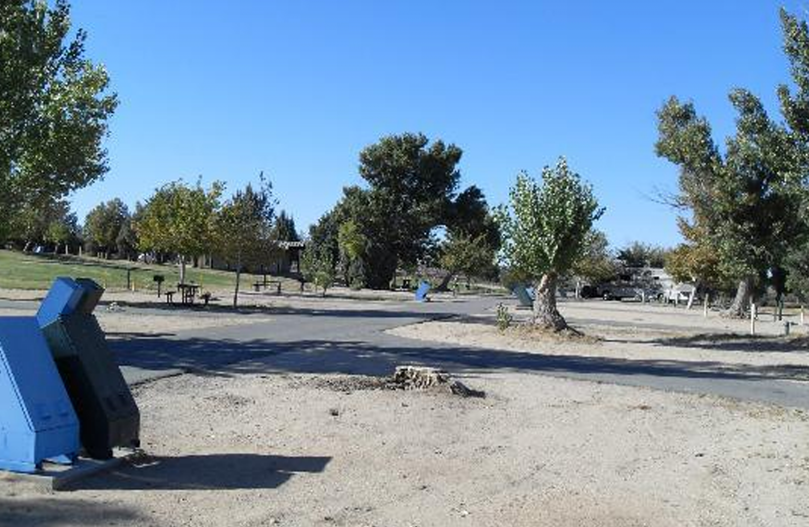 Empty RV camp site area with dump station receptacle.