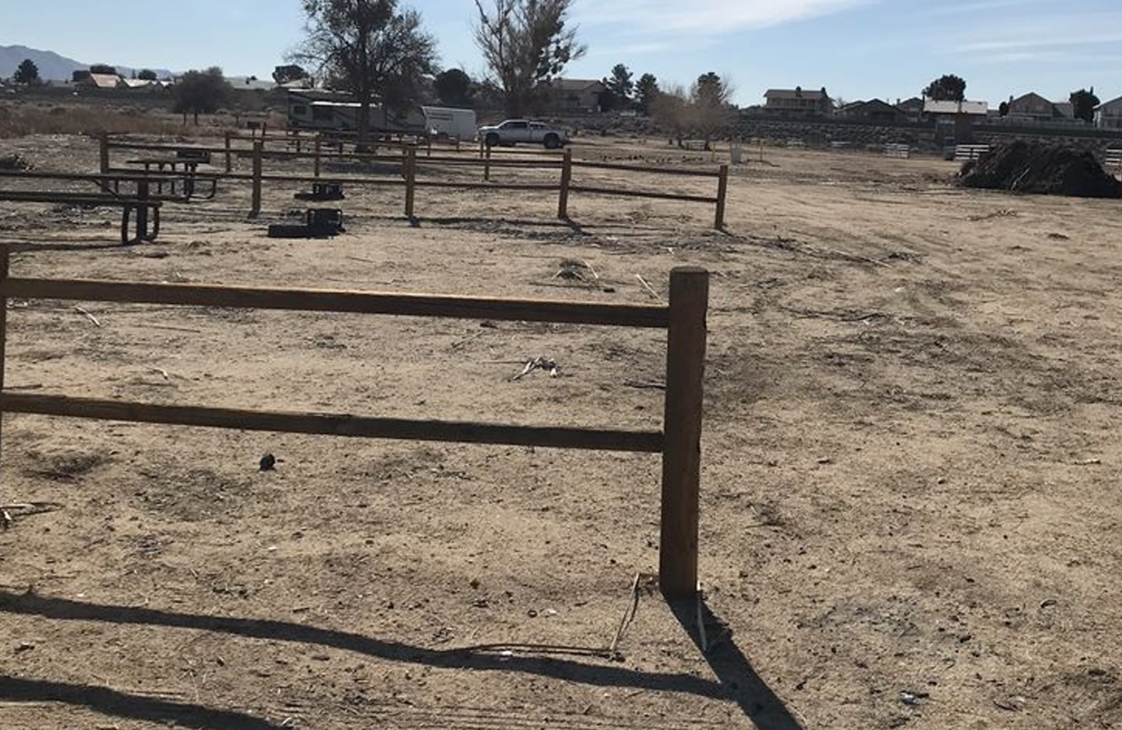Empty dirt horse stalls at Mojave Narrows camp site.