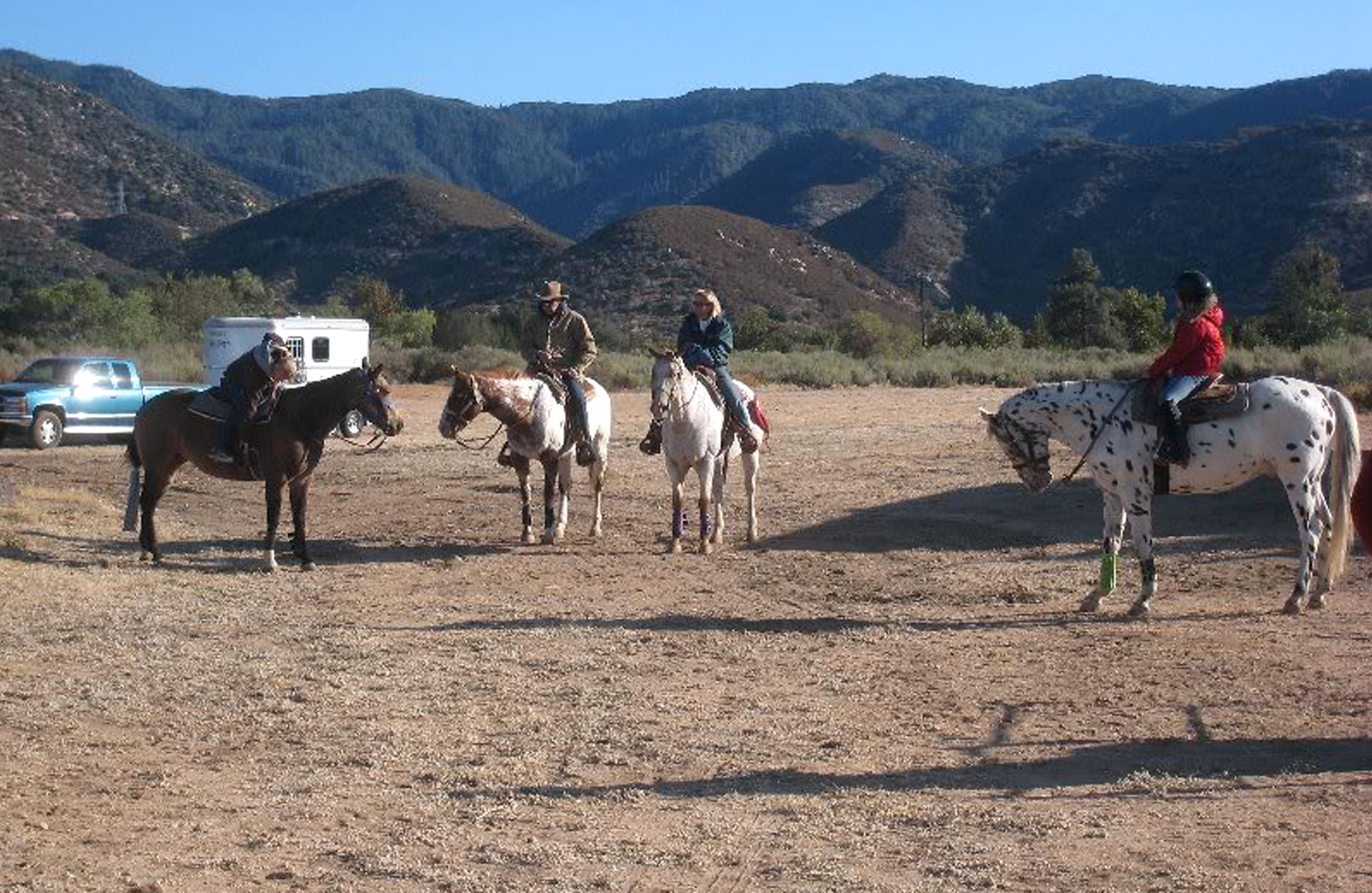 A group of people on horseback in a dirt open area of the park.