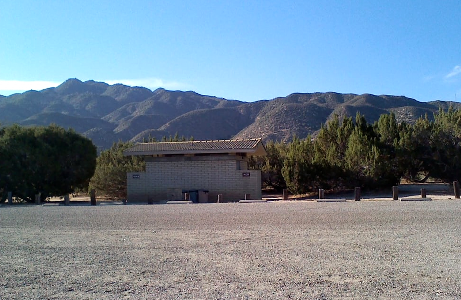 The restrooms at Mojave River Forks. A concrete building sitting on gravel.