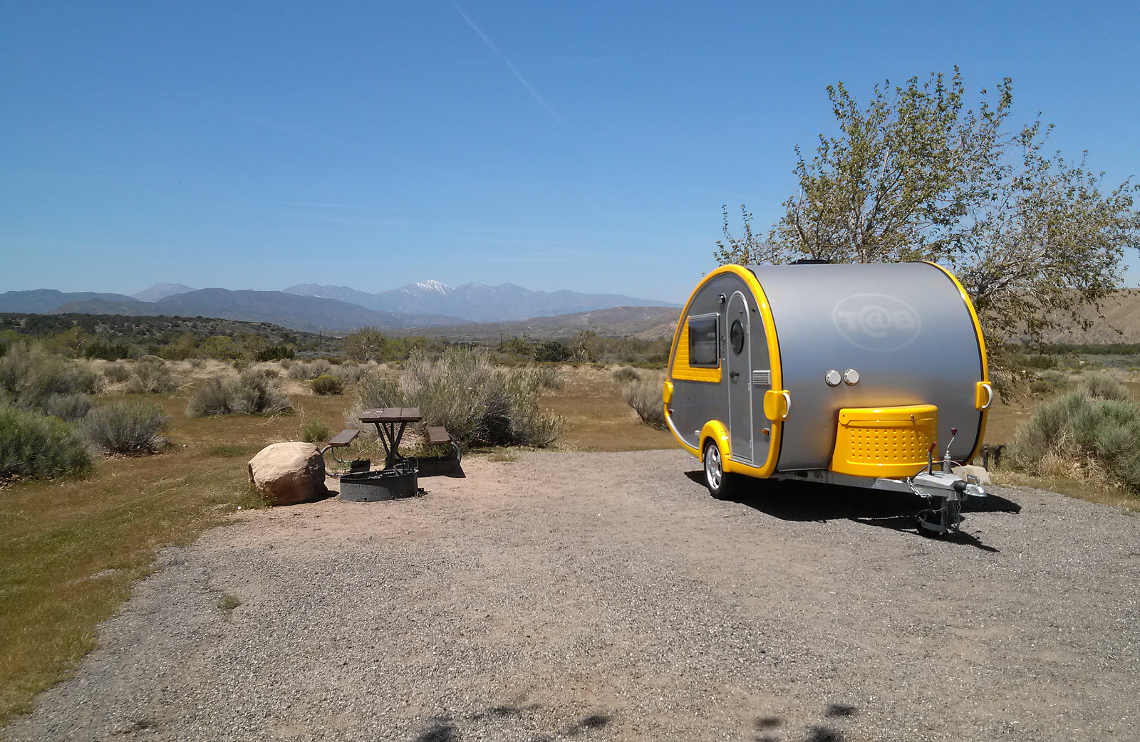 Small Yellow and aluminum retro trailer on a gravel RV slab next to a picnic table on the left in the desert.