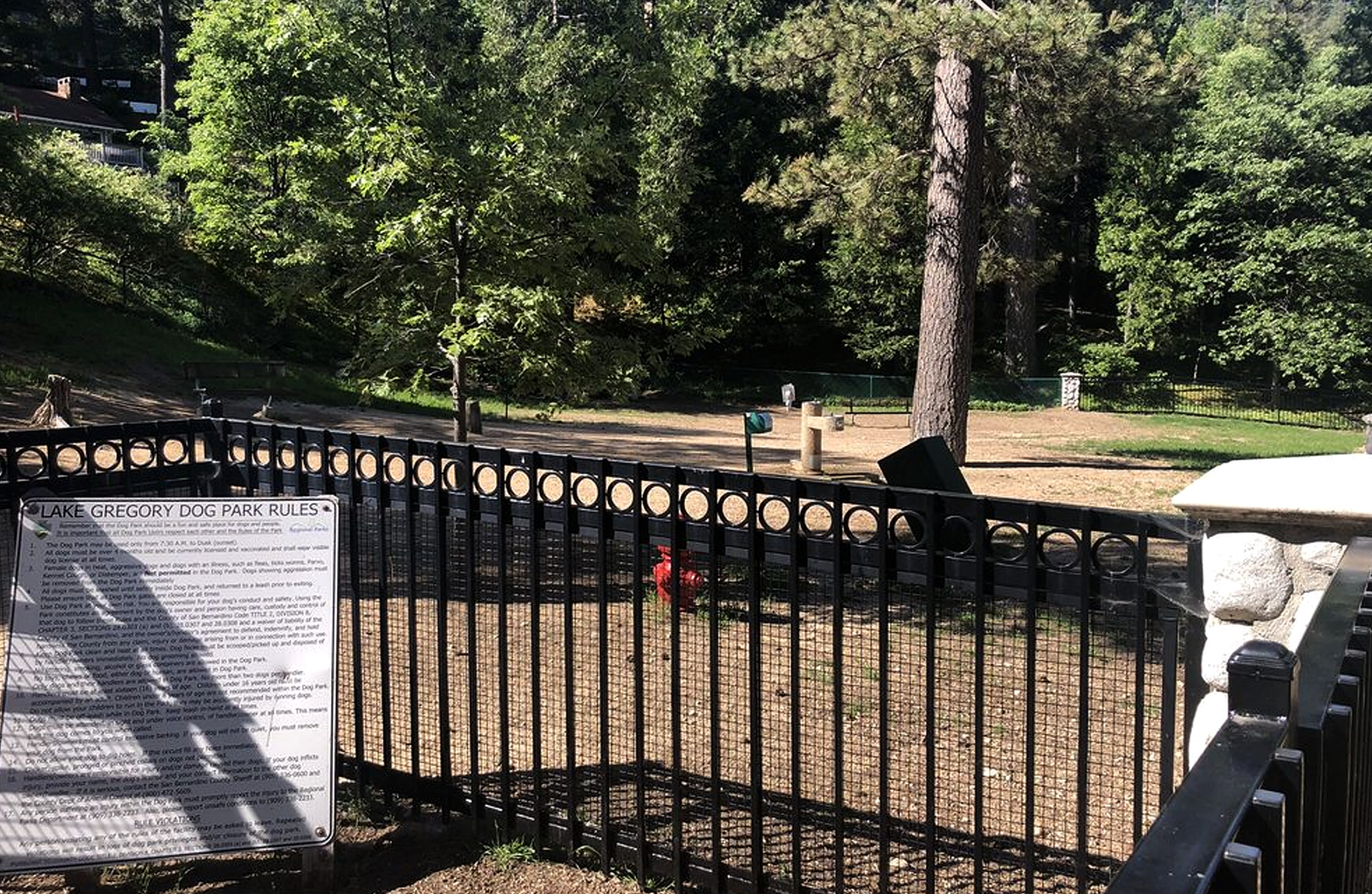 A photo of an empty dog park with metal fence.