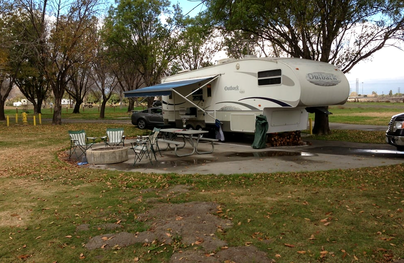 A single camping trailer sits on a concrete slab near grass and a fire ring at Prado park.