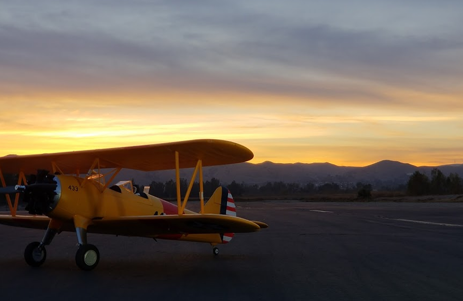 A closeup of a model airplane on the Prado park airfield at dusk.