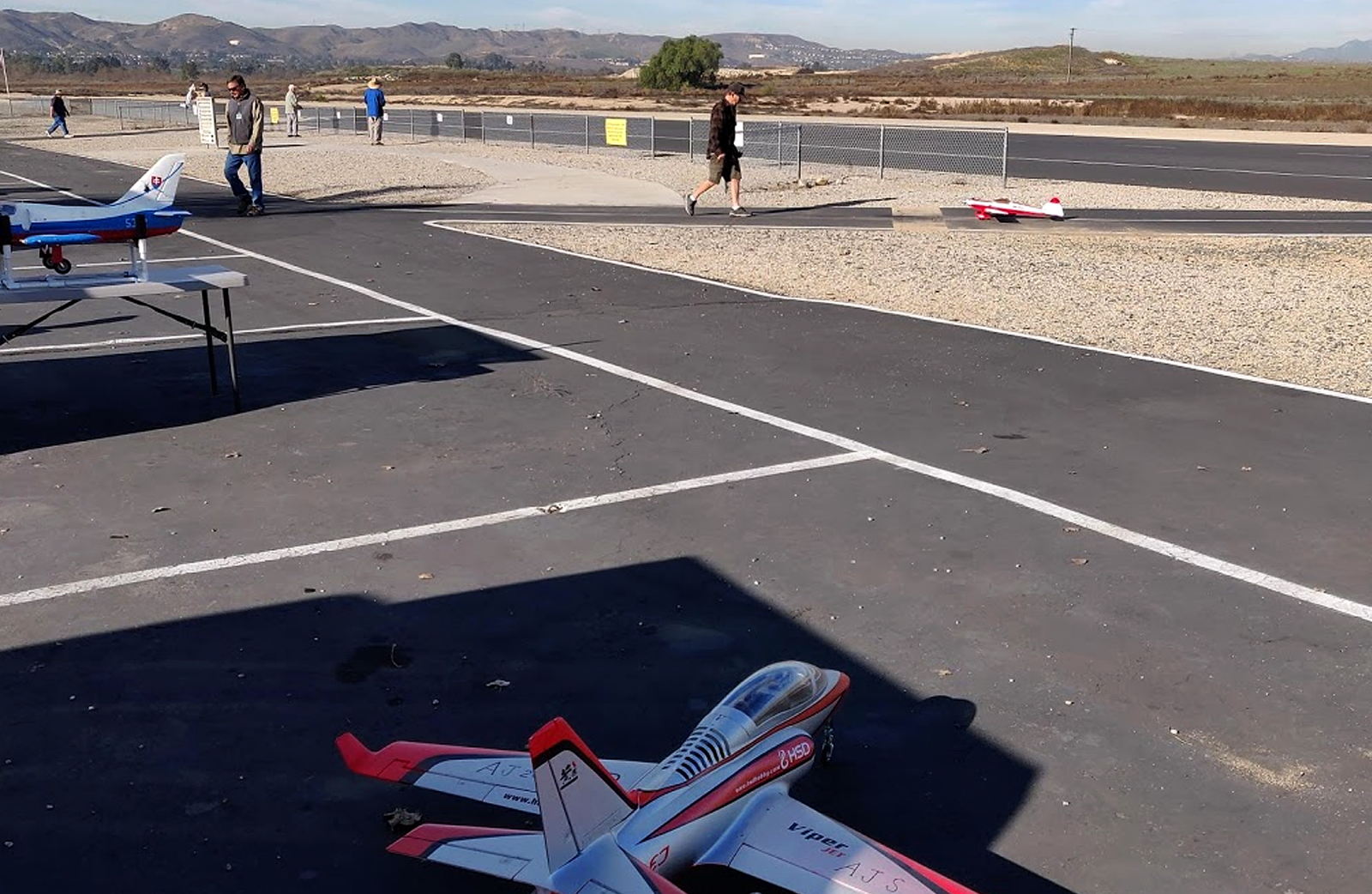Model airplanes sit on the asphalt a Prado park airfield.