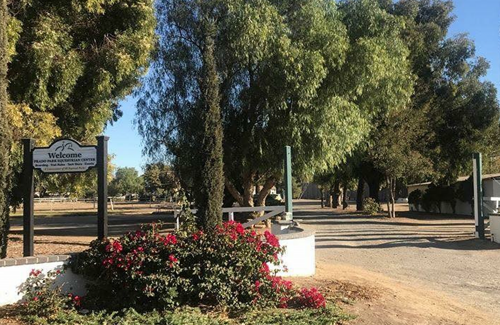 Outside Prado Equestrian Center entrance with flowers and trees.