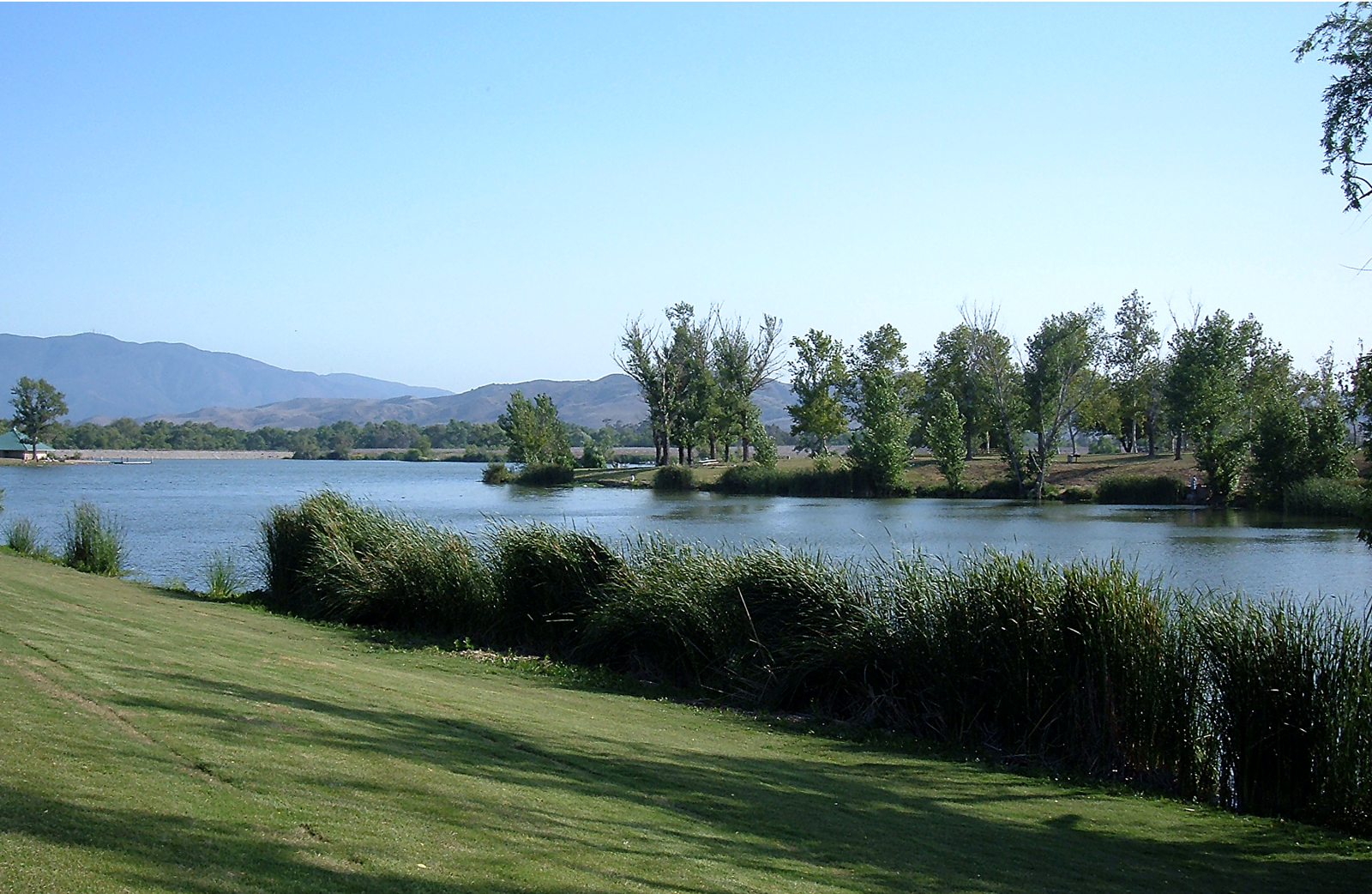A side view of Prado lake with green grass.