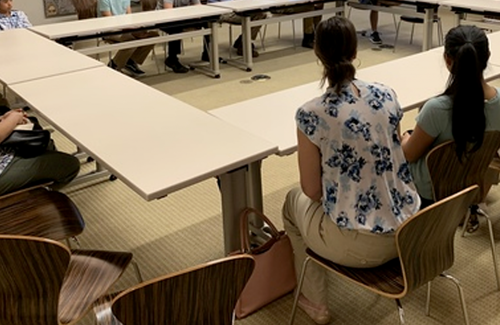 A woman sits at a conference table with her back to the camera.