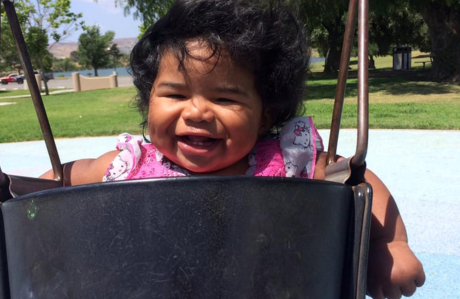 A smiling girl toddler swinging at Prado park.