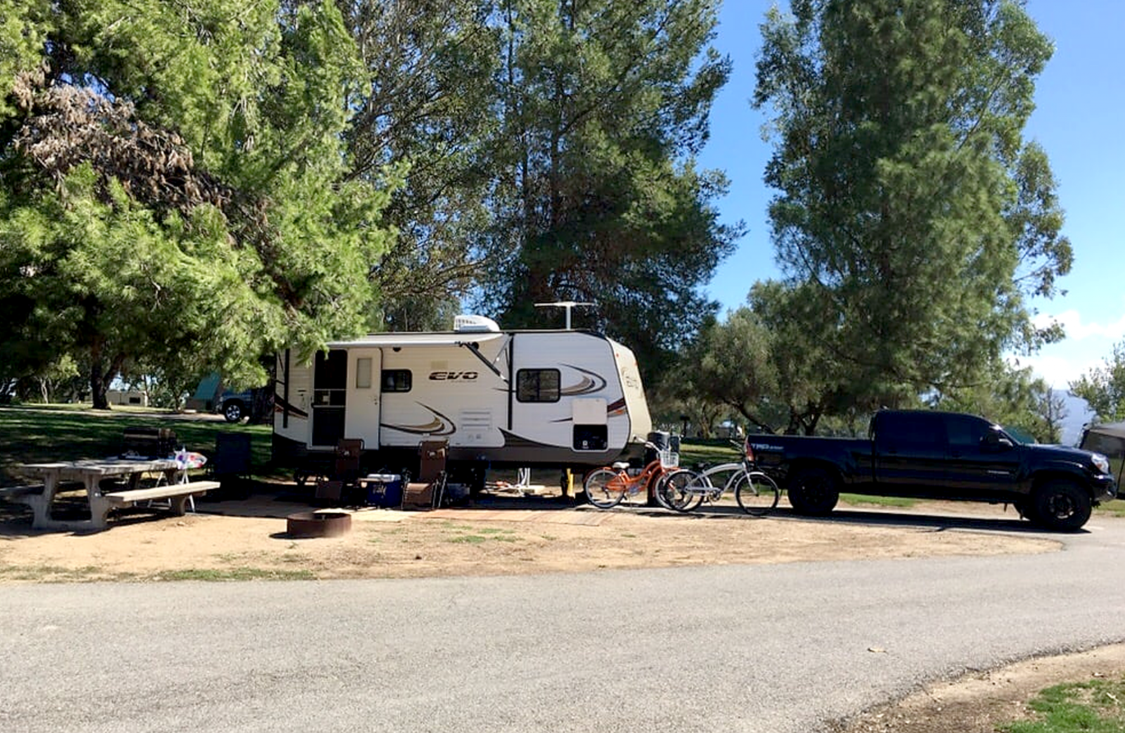 Prado RV camper parked under a tree.