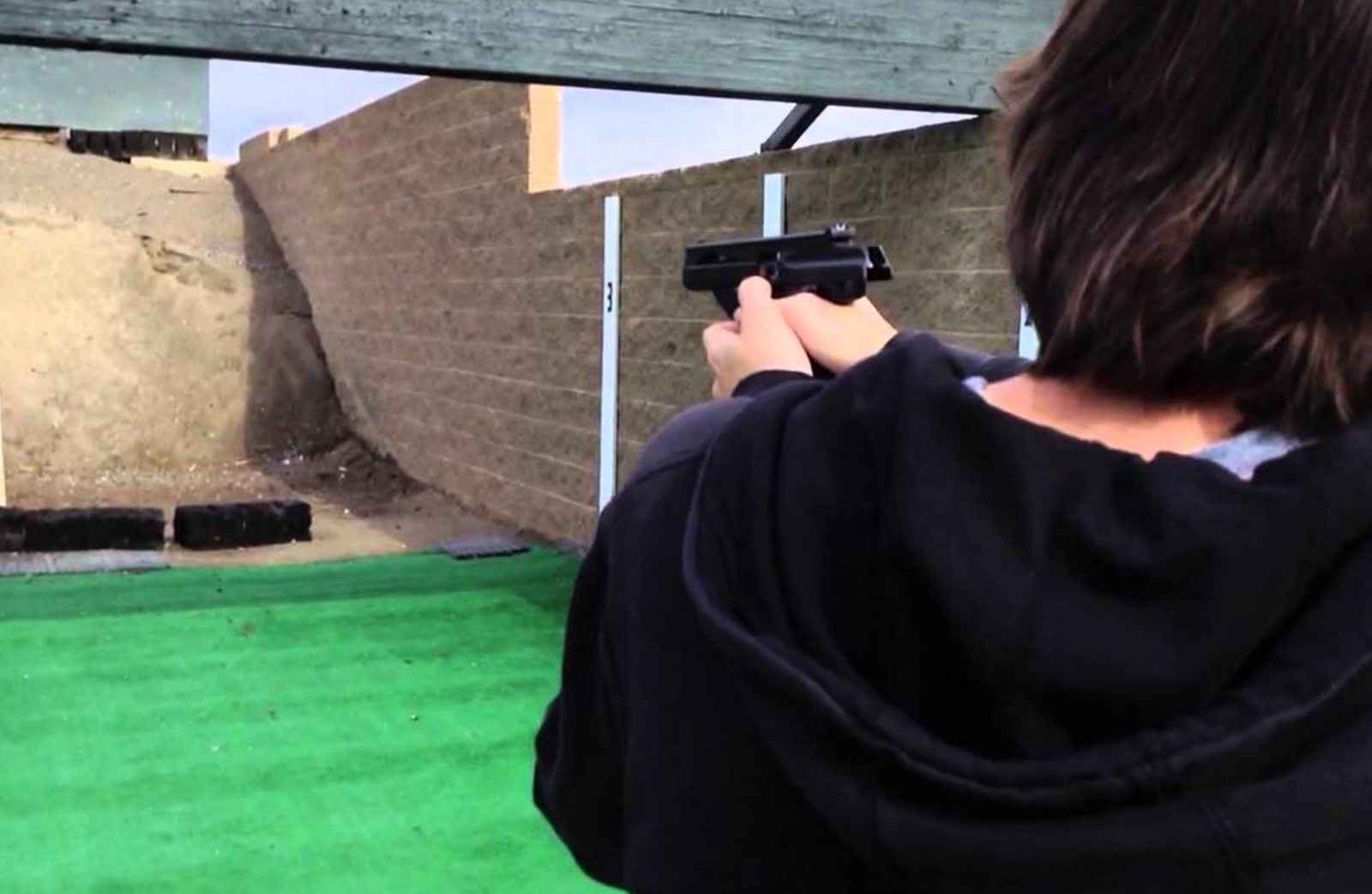 A woman shooting a gun at a target on a gun range..
