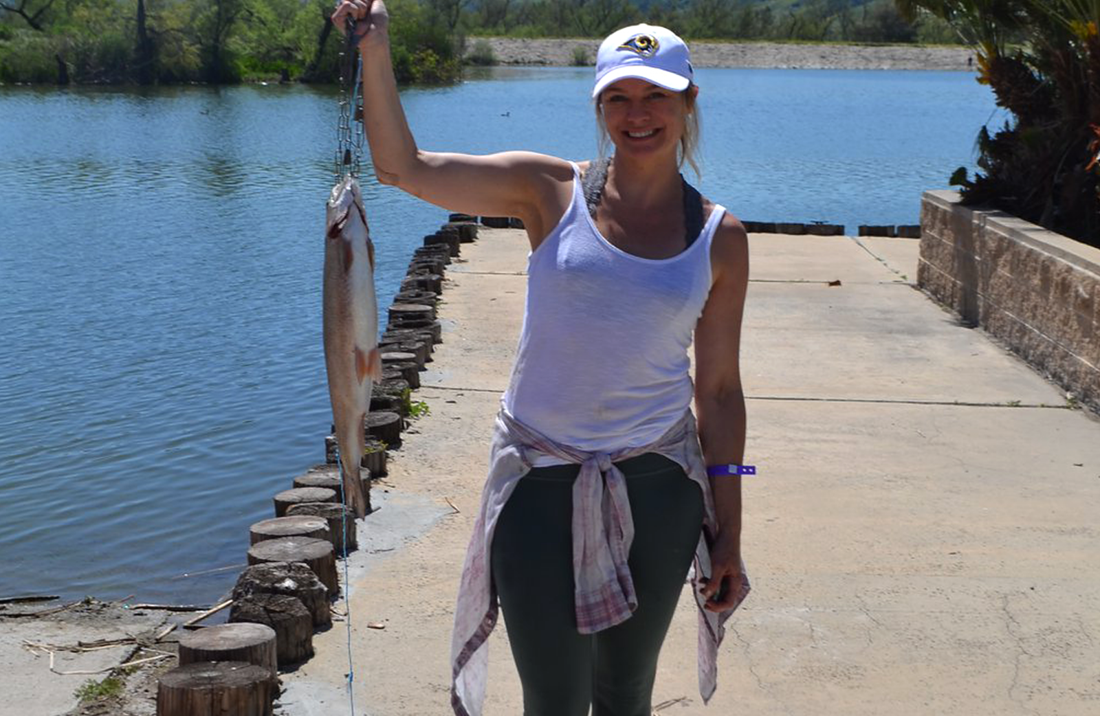 A woman holds up a bass fish she caught at Prado park.