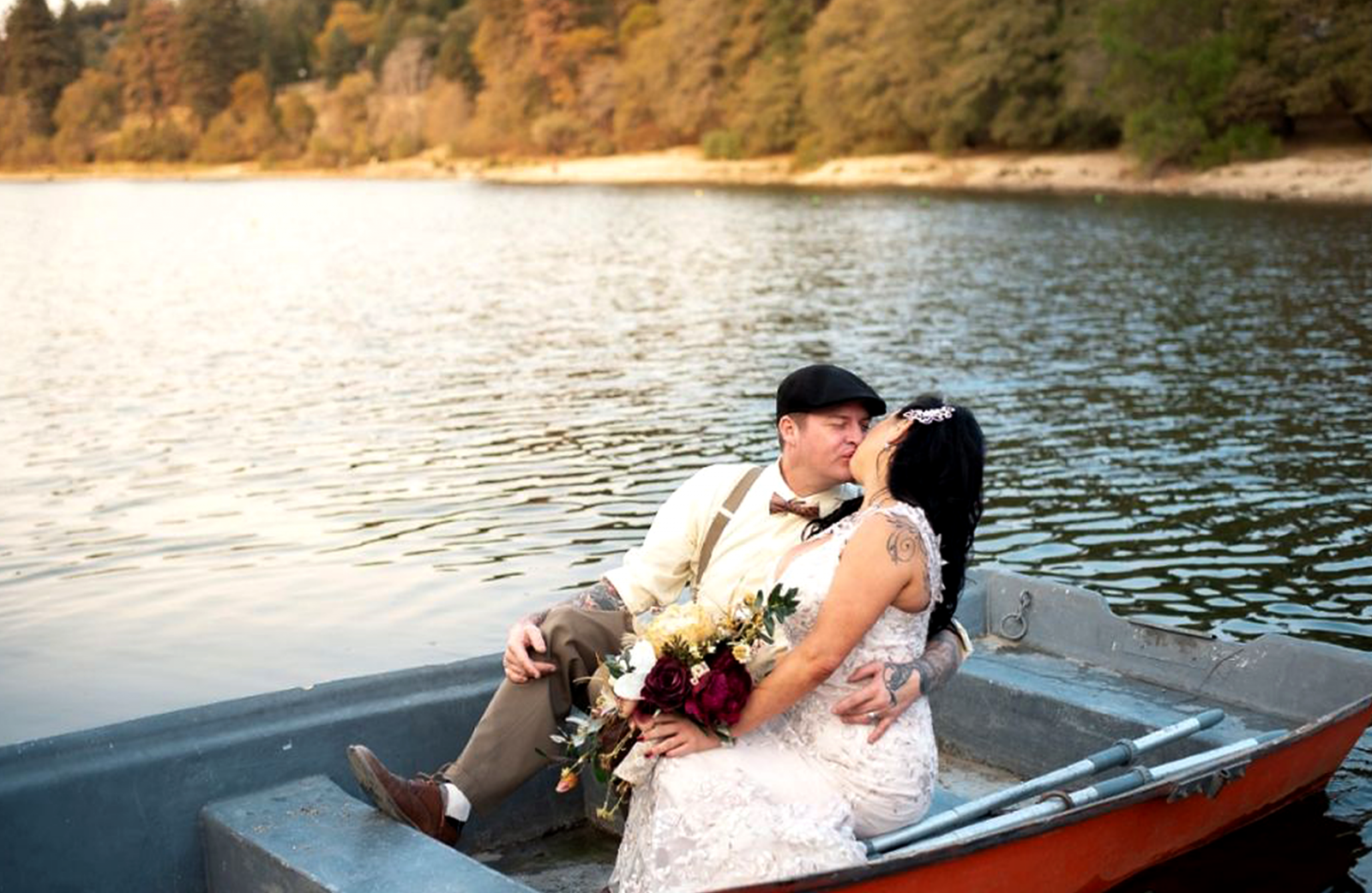 married couple kissing on a boat on a lake
