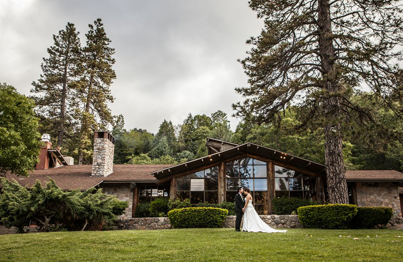 A man and woman on their wedding day as groom and bride kissing in front of the San Moritz lodge.