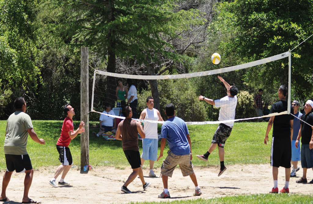 A group of young people playing outdoor volleyball on a sand court surrounded by grass.