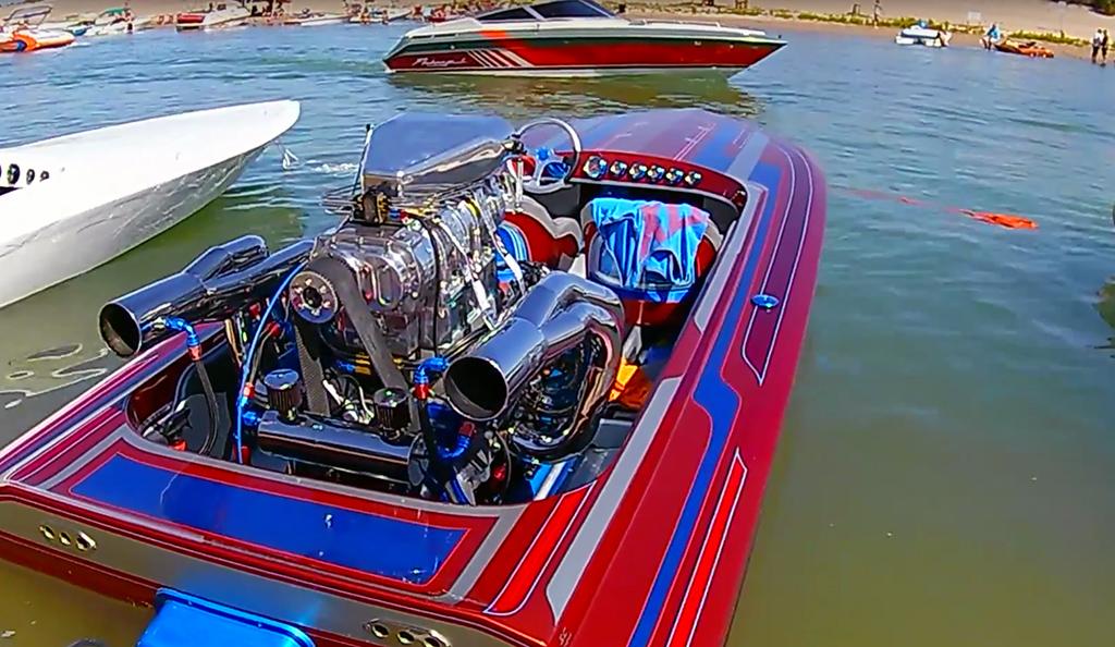 Custom color speed boat rests in dock slip.