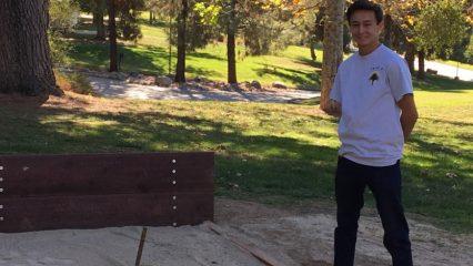Boy Scout Standing near a Horseshoe pit