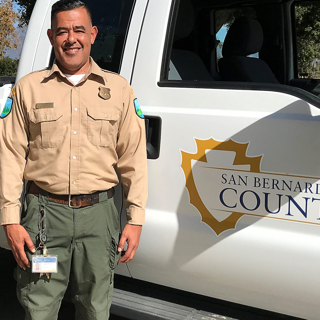 Ranger Joe from Guasti Park standing by the County truck smiling.