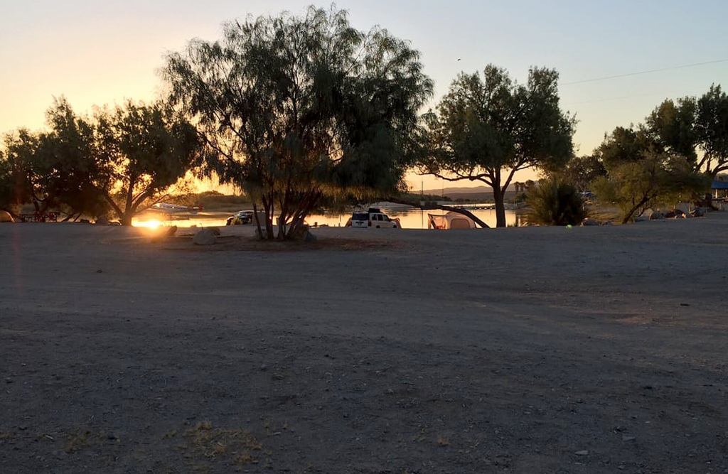 people camping in the distance at sunset