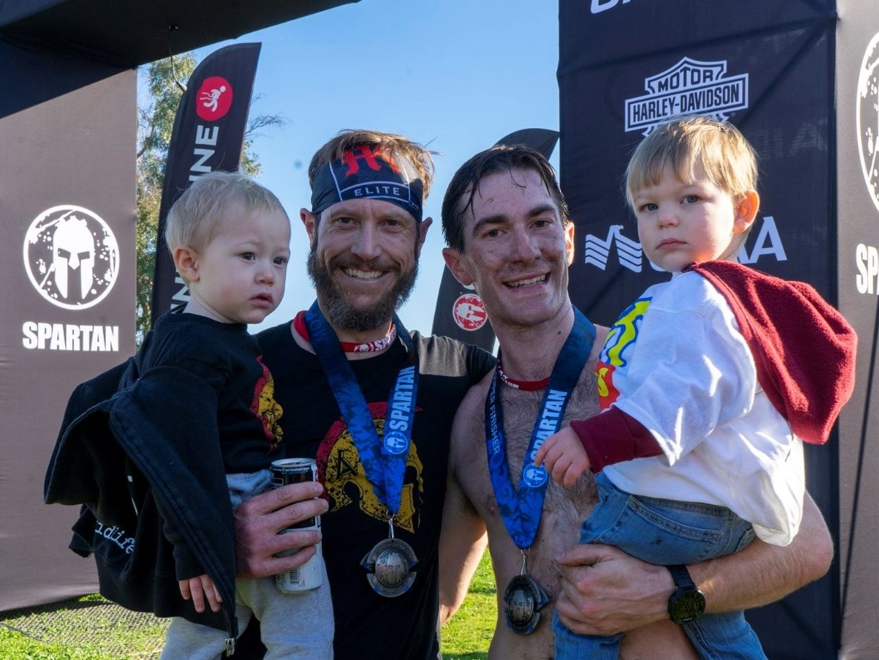 Photo of 2 Men each holding a child at the Spartan Event