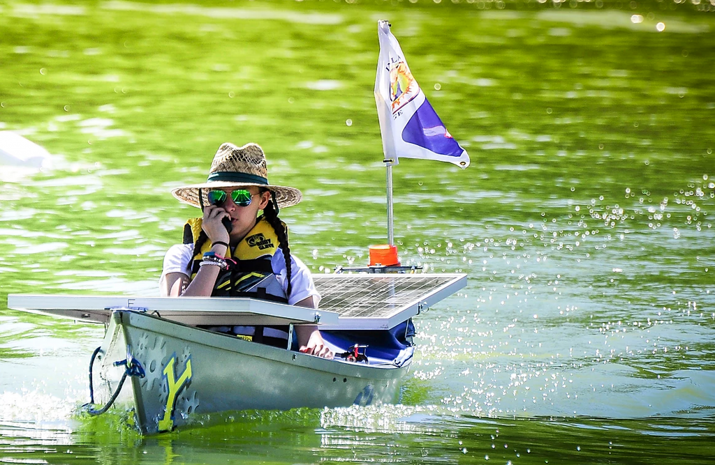 A young high school girl steers a solar-powered boat on a lake.