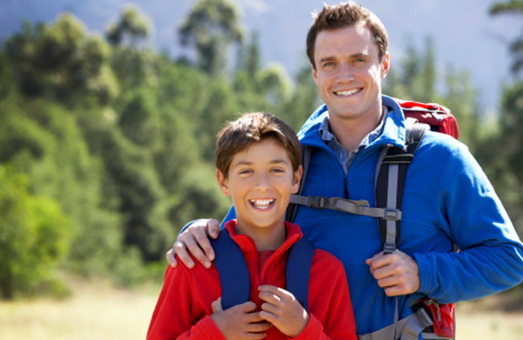 A father with his arm on his son's shoulder and son smile in a park setting.